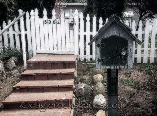 A white picket fence and mailbox